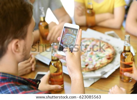 Young man taking photo of pizza and beer with smart phone