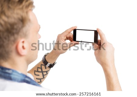 Young man taking photo with mobile phone, isolated on white background for you own image. #257216161