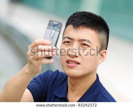 young man taking picture with mobile phone