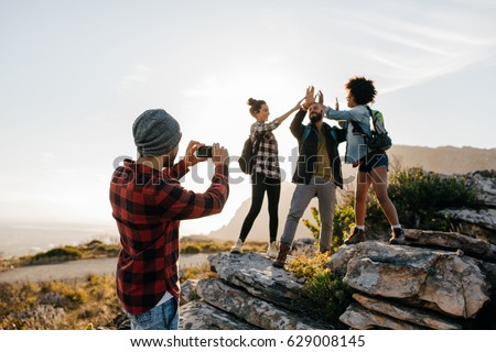 Young man taking pictures of his friends doing high five in countryside while hiking. Group of hikers enjoying during summer vacation.