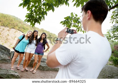 Young man taking pictures of young ladies on a hike at Great Falls National Park in Virginia