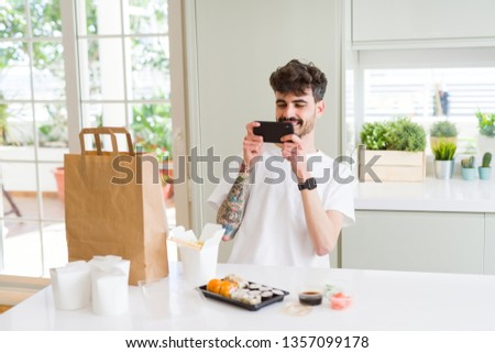 Young man taking pictures with smartphone of sushi asian food from take away delivery