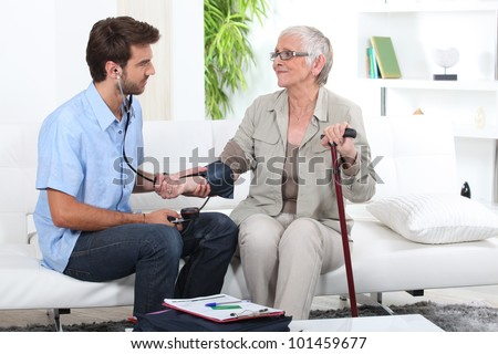 Young man taking the blood pressure of an older lady