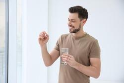 Young man taking vitamin indoors
