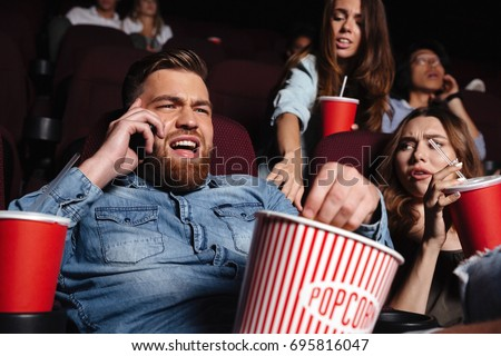 Young man talking loud on mobile phone while watching movie at the cinema and disturbing audience
