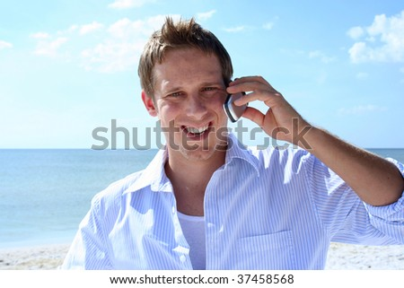 Young man talking on phone on the beach