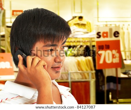 Young Man Talking On The Phone In Front Of A Store Which Has A Sale