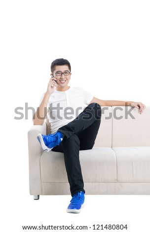 Young man talking on the phone on sofa