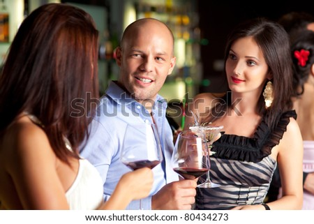 young man talking to beautiful women at the bar