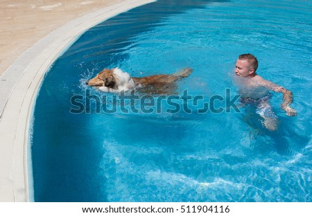 Young man teaching collie dog to swim in blue pool #511904116