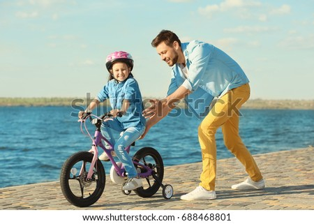 Young man teaching his daughter to ride bicycle outdoors near river