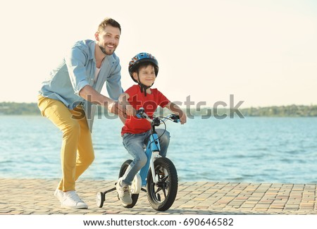 Young man teaching his son to ride bicycle outdoors near river