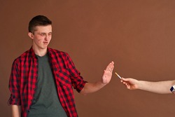 young man, teenage student, holds out his hand like stop sign, refusing cigarette with outstretched hand destitute person on brown background. Giving up a bad habit. Fight against smoking.