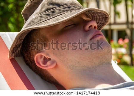 Young man, teenager, student, closeup sits in a hat on a deck chair and rests. Concept of rest, relax, rest. #1417174418