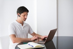 Young man teleworking from his home on his laptop and wearing an earpiece.