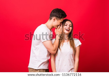 Young man telling a secret to a woman over a red background