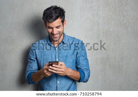 Young man texting message on smart phone isolated on grey background. Smiling latin man holding smartphone and looking at it. Happy hispanic man writing a message on the  phone.