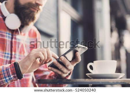 Young man texting on his smartphone in the city. Close up of cheerful adult using mobile phone in a cafe