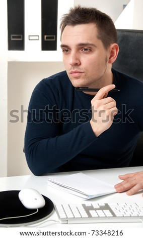 Young man thinking in front of his computer in the office ambient