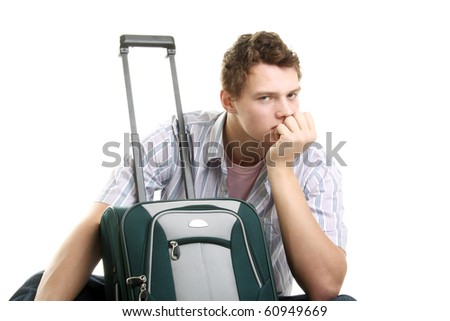young man thinking near the suitcase in studio
