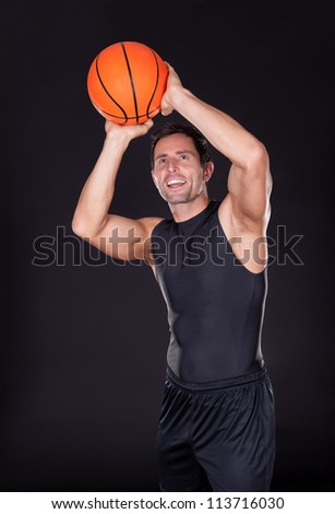Young Man Throwing Basketball Isolated On Black Background