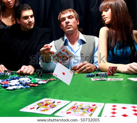 Young man throwing chips on the table while playing cards