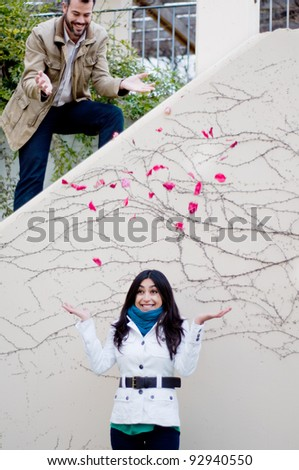 Young man throwing flower petals on his girlfriend