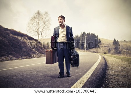 Young man tired of walking and carrying suitcases on a country road