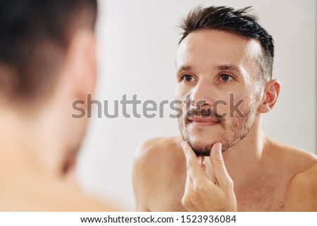 Young man touching his chin and checking his beard he is trying to grow out