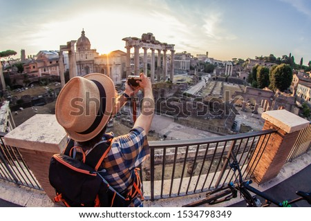 Young man tourist backpacker with bike taking pictures with vintage camera at Roman Forum at sunrise. Historical imperial Foro Romano in Rome, Italy from panoramic point of view.