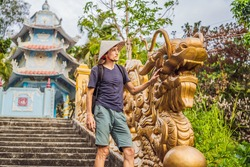 Young man tourist in a traditional Vietnamese hat travels to Vietnam