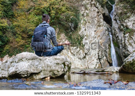 Young man tourist in casual clothes with backpack sits in picturesque place on stone overlooking waterfall and meditates alone. Concept of self-knowledge of self-improvement and self-identification