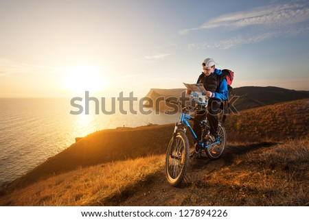 young man tourist on a bicycle traveling at night in the mountains