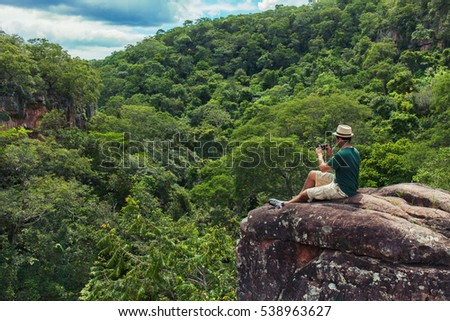 Young man tourist sitting on the rock at the top of mountain and taking photo with smartphone of a green tropical valley. 25-30 years old with t-shirt, shorts and hat.