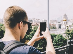 Young man tourist taking a shot in moscow on phone