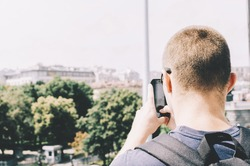 Young man tourist taking a shot of the moscow on phone