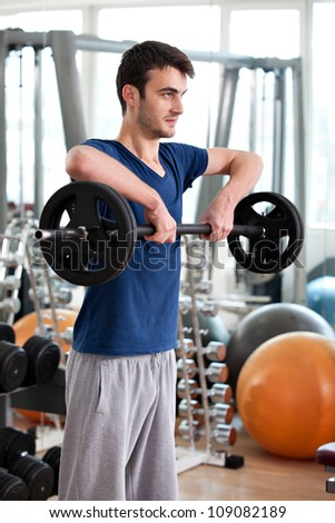 young man training in the gym: shoulders - upright barbell row