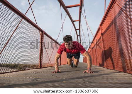Young man training push ups in pedestrian bridge