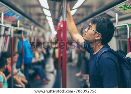 Young man traveler is visiting at Hongkong by subway MTR train. The Mass Transit Railway is the rapid transit railway system in Hong Kong.