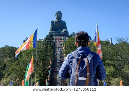 Young Man traveling backpacker, Asian traveler visit the Tian Tan or Big Buddha located at Po Lin Monastery in Ngong Ping Lantau Island. landmark and popular for tourist attractions in Hong Kong