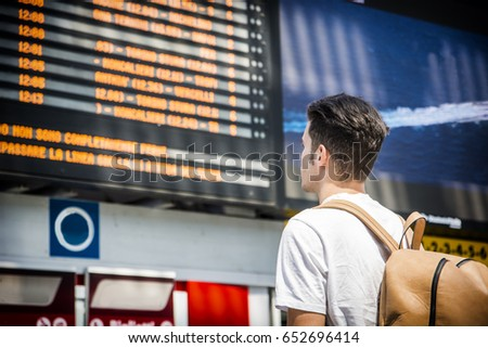 Young man traveling, reading big electronic train timetable in railway station, seen from behind