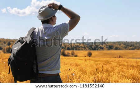 Young man travels with a backpack on a summer day outdoors