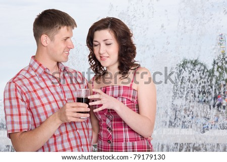 Young man treats his girlfriend to a cool drink. In the background, splash fountain. Hot summer.