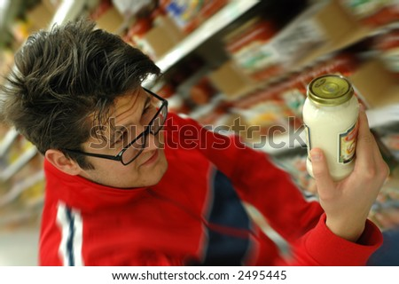 Young man trying to read a label at the supermarket.