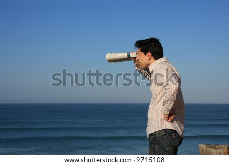 Young man trying to see something with a newspaper binocular