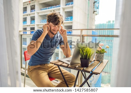 Young man trying to work on the balcony annoyed by the building works outside. Noise concept. Air pollution from building dust Foto stock ©