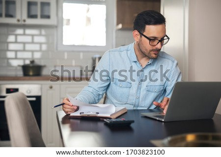 Young man typing on a laptop and doing paperwork from home.