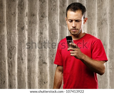 young man typing on a mobile phone against a wooden wall