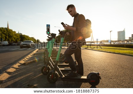 Young man unlocks an e-scooter with his mobile phone. Electric scooter new way city mobility. Green transportation. Sustainable climate neutral cities goals. Green mobility sustainable transportation