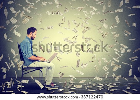 Young man using a laptop building online business making dollar bills cash falling down. Beginner IT entrepreneur under money rain. Success economy concept